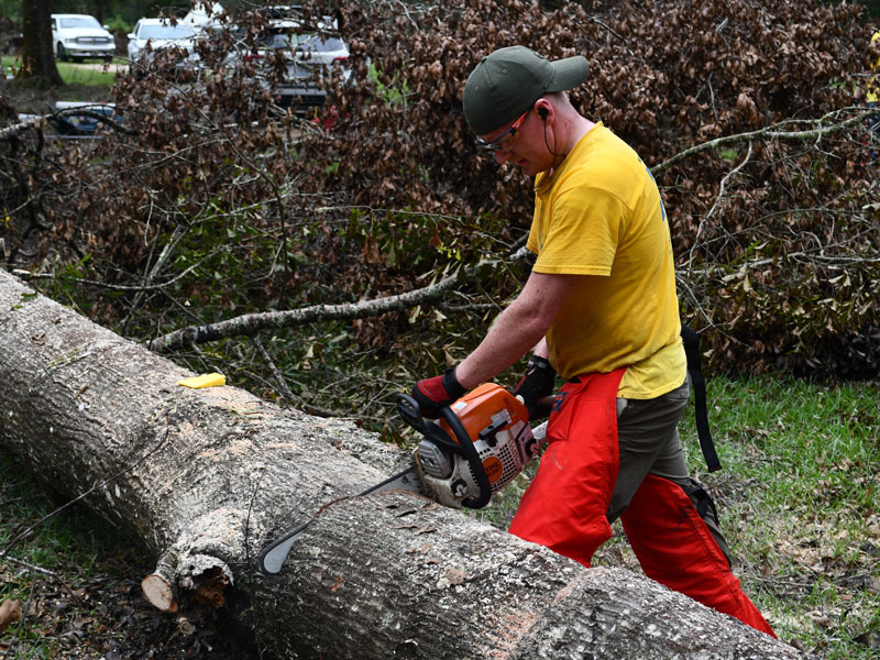 Spencer Youngberg from the Tallahassee Florida Stake works the chainsaw.