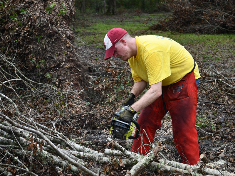 Trevor Bryan from the Tallahassee Florida Stake works with a chainsaw.