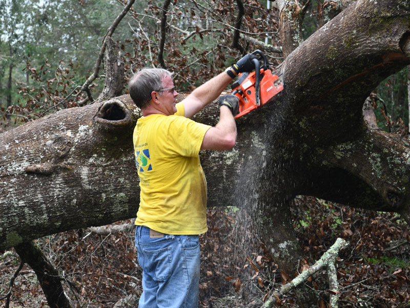 Rodney Schank of the Tallahassee Florida Stake cutting branches.